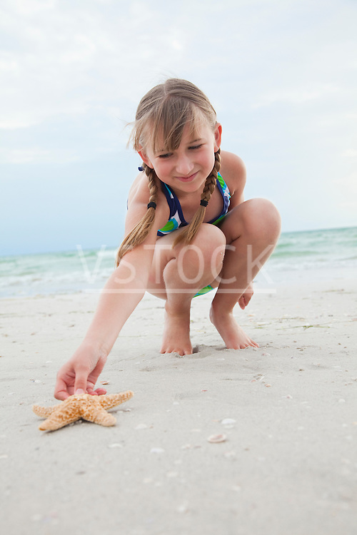 USA, Florida, St. Pete Beach, Girl (8-9) reaching for starfish on beach
