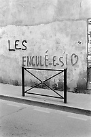 "France. Gironde department. Bordeaux. Graffiti on the wall. A person has writen the words"" Les enculés"" (motherfuckers) and drawn a heart. A sidewalk's barrier. 23.03.2015 © 2015 Didier Ruef"