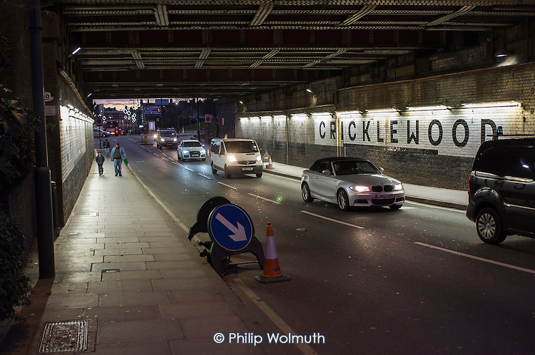 Road traffic and pedestrians pass under a railway bridge in Cricklewood, London.