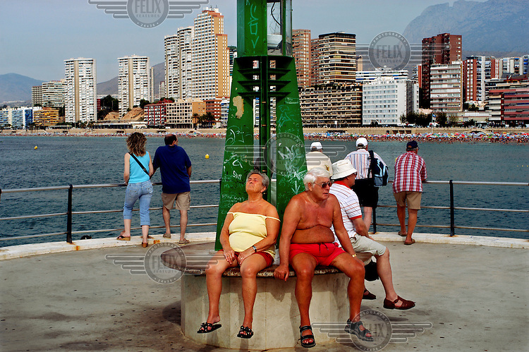 An elderly couple top up their suntans at the end of Colombus Boulevard, with Poniente beach in the background.