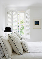 Louvered shutters over the window of this contemporary bedroom ensure privacy while bathing the room in natural light