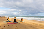 People taking a yoga class from an instructor with Maui Yoga Shala on the beach at Lower Paia Park, Paia, Maui, Hawaii, USA