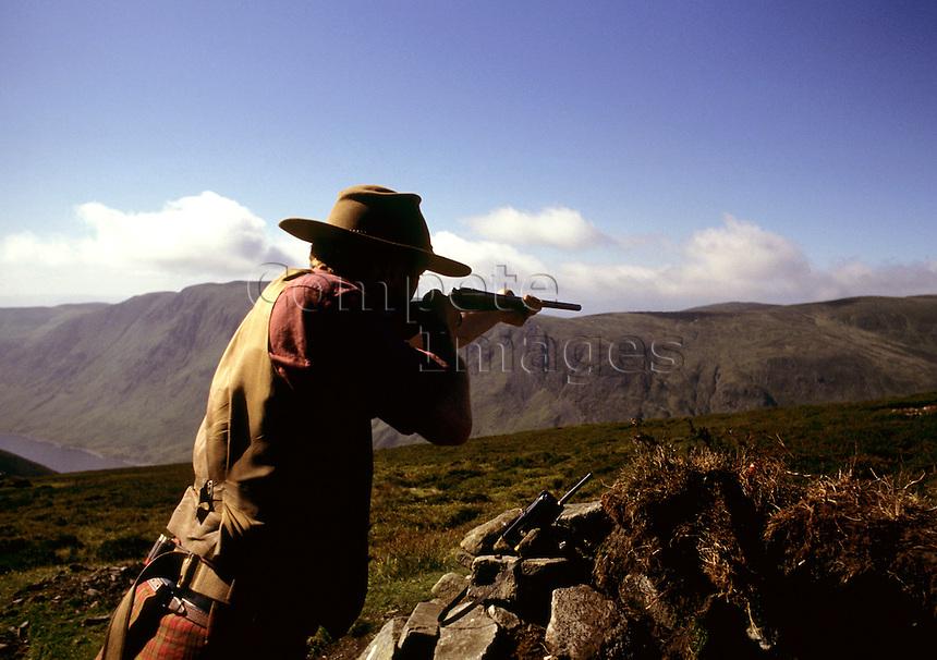 Man aiming gun while hunting