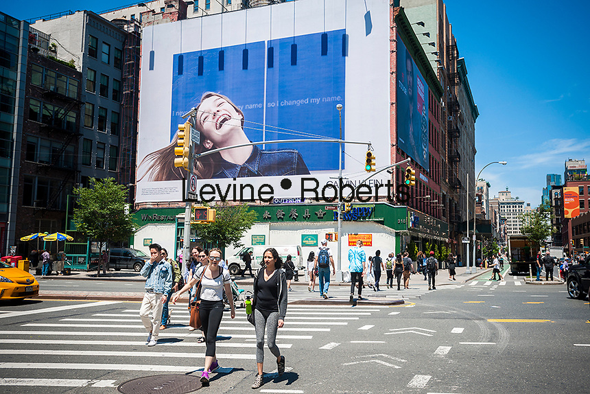 """People cross Houston Street below a billboard advertising the Calvin Klein brand of denim shirts in the Soho neighborhood of New York on Friday, June 9, 2017. Klein's advertisements have been using artwork behind the models with this one featuring """"Changed My Name"""" 1988 by the artist Richard Prince. (© Richard B. Levine)"""