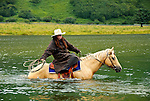 Rochelle riding across the Pasagshak River, Kodiak Island, Alaska