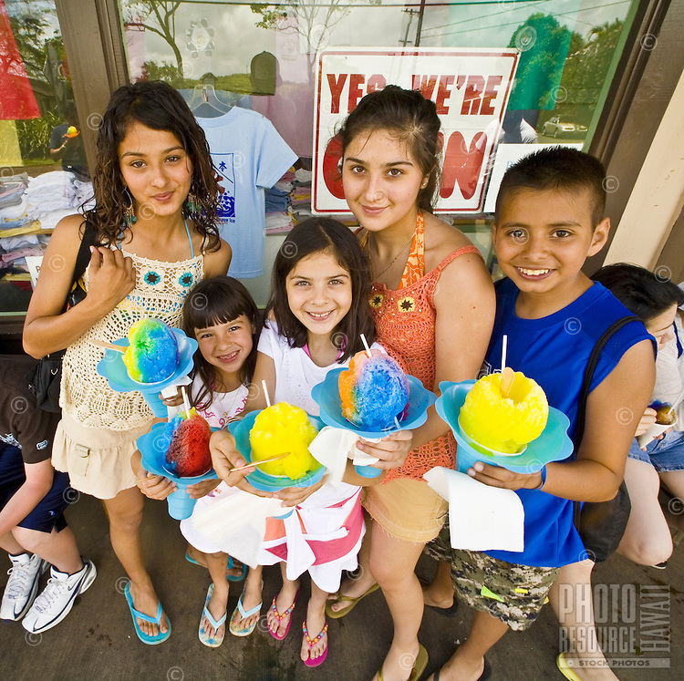 Kids eating Matsumoto's Shave Ice, a Haleiwa tradition since 1951, still best way to cool off on Oahu's North Shore, Hawaii