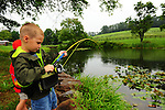 Two young boys hook a fish while fishing in a pond in the summer in northeast PA in the rain.