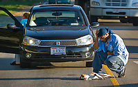 A man kneels at the body of a dog killed when it was hit by his car on a busy city street during rush hour. Sitting in the car crying is the dog's owner.