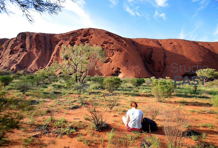 A woman reads by Ayers Rock, or Uluru, Northern Territory, Australia, on December 30, 2008. Photo by Lucas Schifres/Pictobank