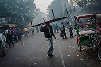 OLD DELHI, INDIA, JANUARY 11, 2016: A worker carries to put away a charpoy, or makeshift bed, rented to people at a sleep market on January 11, 2016 in Old Delhi, India. <br /> Daniel Berehulak for The New York Times