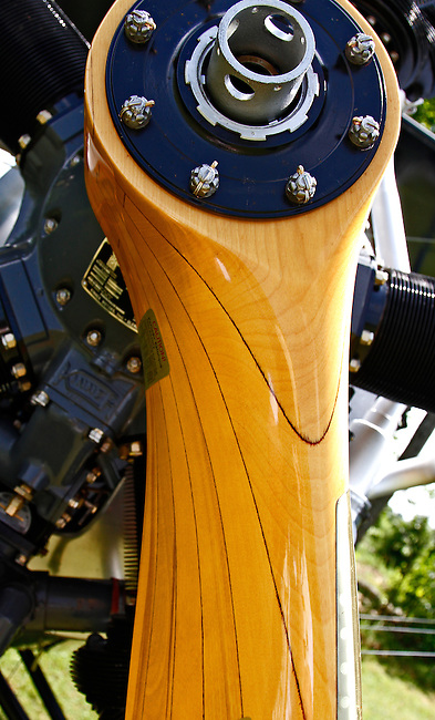 A macro photograph of a highly-polished, wooden propeller on the Kinner Radial Engine of a 1939 Meyers OTW (out-to-win) bi-plane showing the propeller's wood grain and lamination at the Galway Wings 'n' Wheels 2010 Showcase.