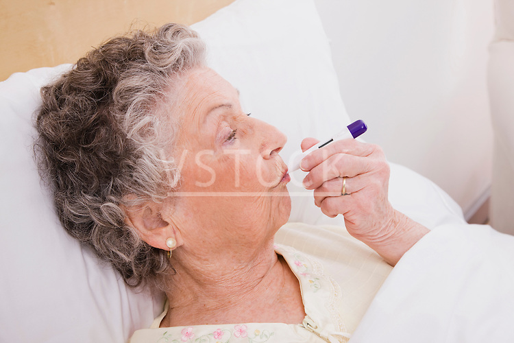Senior woman with thermometer in mouth