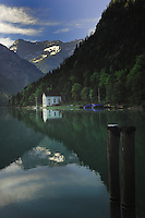 Lake side white cottage,trees and mountains reflected in Lake Plansee near Reutte, Austrian Alps. Austria.