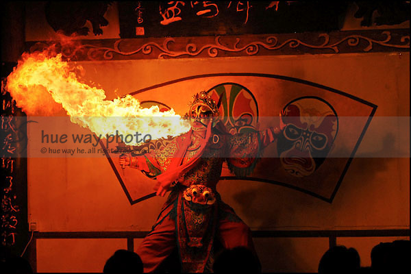 A dramatic long fire flame spitted out by a traditinal Chinese Opera performer, in a Chinese tea house.