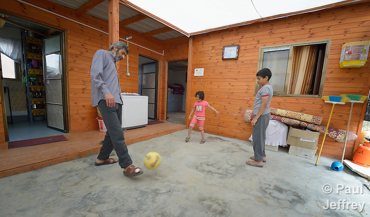 Fawzi Abu Jame'a plays football with his 7-year old daughter Raghad and 12-year old son Ahmad in the courtyard of their new transitional house built for them by Catholic Relief Services in Khan Yunis, Gaza. Houses in the area were destroyed by the Israeli military during the 2014 war between the state of Israel and the Hamas government of Gaza. CRS is building hundreds of transitional homes where families can live for several years until they can rebuild their own permanent home.