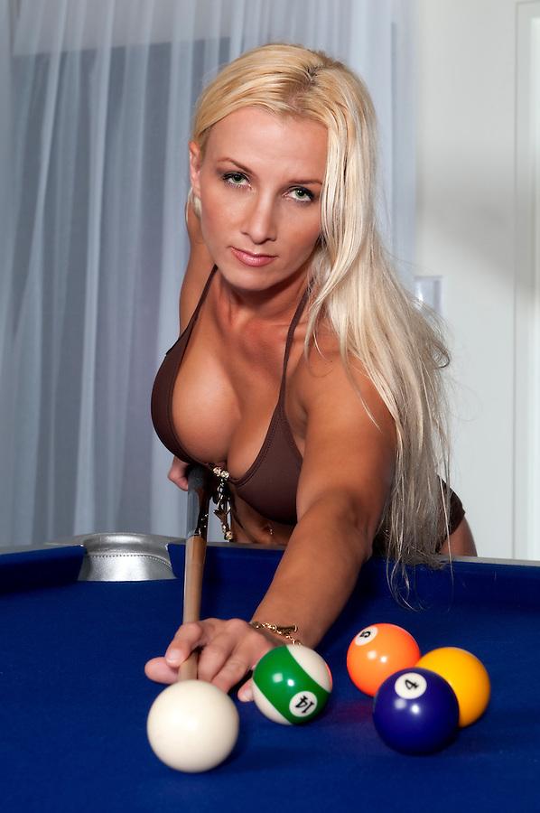 30 something caucasian woman playing pool in bikini.
