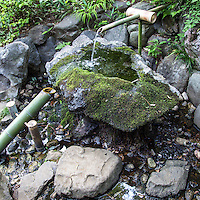 Tonogayato Garden - Shishi odoshi or deer scare is a gereric device made to scare away animals such as deer from damaging gardens and even a farm.  Sozu is a special water fountain used specifically in Japanese gardens.  Sozu consists of a bamboo tube pivoted to its balance point - its heavier end is down and resting against a rock while water fills into the other end of the bamboo tube.  After the water has accumulated this moves the tube's center of gravity past the pivot, causing the tube to rotate and release water. The heavier end falls back against the rock making a sharp sound, and the cycle repeats. This noise is intended to startle deer which may be grazing on plants in the garden.