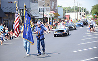 NWA Democrat-Gazette/FLIP PUTTHOFF <br /> GRAVETTE DAY PARADE<br /> Jim Brooks (left) and Darrel Mercer carry flags during the parade Saturday Aug. 10 2019 at the 126th annual Gravette Day. The parade along Main Street featured the Gravette Lions marching band, football team, cheerleaders and other groups, plus an array of emergency responder vehicles. A car show, Dutch oven cook-off and arts and crafts were part of the annual Gravette Day gathering.