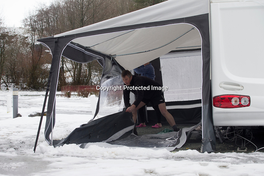 "28/03/16 <br /> <br /> Awning is taken down after weight of snow buckles poles.<br /> <br /> Holiday makers camping in the Derbyshire Peak District woke up to an unexpected white blanket this morning, thanks to Storm Katie.<br /> The covering of snow meant that many campers cut short their plans for a long weekend away, to brave the icy roads and head home early on Monday morning.<br /> But it wasn't all bad news for some of the younger guests at Grin Low Caravan Site in Buxton.<br /> Three-year-old Greta Williams made the most of the morning's surprise by building a snowman and enjoying snowball fights with her aunt Claire Jones. <br /> Claire said it was the first time she had been camping in the snow. <br /> ""It was completely unexpected but it's made it a trip to remember,""she said. <br /> ""Greta really enjoyed making the snowman, but I think we'll head back home now in case any more falls.""<br /> For Chris and Lorraine McCoy the first they knew of the snow was when they woke up and stuck their heads out of their tent.<br /> They had travelled to Buxton from Warwickshire with their four-year-old son Joe, to enjoy a weekend break.<br /> ""It's all part of the adventure,"" said Chris. ""It's a bit cold in the tent but we'll soon warm up, and it's made the surrounding countryside really beautiful.""<br /> <br /> All Rights Reserved: F Stop Press Ltd. +44(0)1335 418365   +44 (0)7765 242650 www.fstoppress.com"