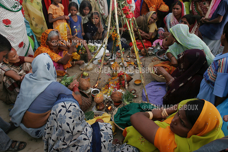 ".VARANASSI, UTTAR PRADESH, INDIA - SEPTEMBER 26, 2005 : Women perform the ritual of Jivitputrika Vrat on the bank of the Ganges in Ramnagar, on september 25, 2005. Ramnagar sits accross the Ganges from Varanasi. Varanassi, also named Benares or Kachi, is one of the holiest place for Hindus in India, drawing millions of pilgrims every year. They come to prey to along the temples lining the ghats, and purify themselves in the ""Holi Ganga"". It always has been an auspicious place to die, since expiring here offers 'moksha', liberation of the circle of life and death. (Photo by Jean-Marc Giboux)"