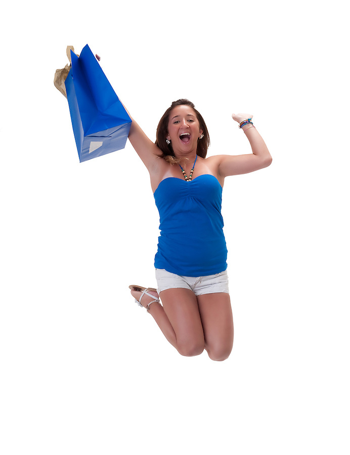 Young hispanic woman jumping high, very happy with shopping bag.