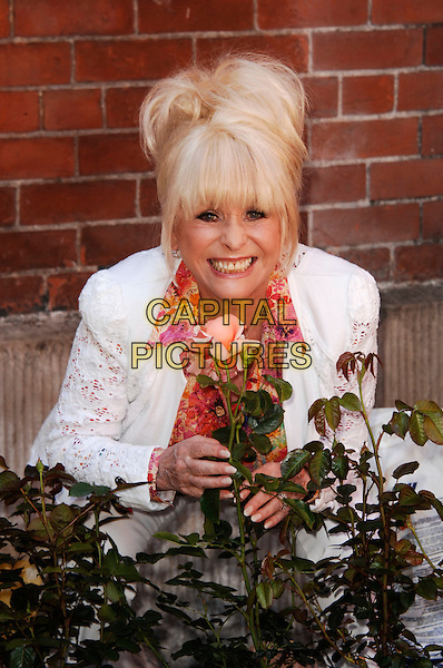 Barbara Windsor.photocall to launch the St Paul's Gardens appeal which aims to repair damage to the church's gardens caused by land subsidence. She poses whilst planting a Barbara Windsor Rose, St Paul's, Bedford Street, Covent Garden, London, England..May 25th, 2012.babs half length white suit blazer pink shirt print smiling flower plant .CAP/WIZ.© Wizard/Capital Pictures.