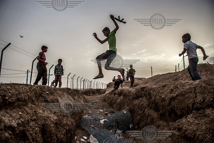 Children displaced from Mosul by fighting between government forces and ISIS militants leap across a drainage ditch in Khazir IDP.