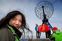 photograph by XAVIER CERVERA 05/2010.Endora Zhang, a business woman and a broker from Beijing, enjoys second stop (after Tromso) above Arctic Polar Circle in Nordkapp, on the way to Svalbard archipielago, Norway. Many chinese tourists show very proudly their national flag