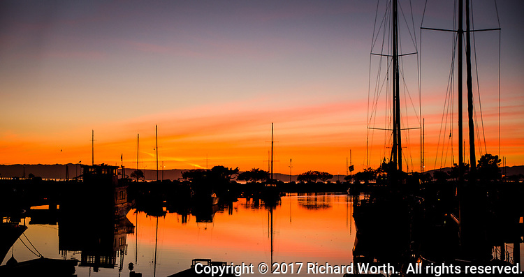 A blazing sunset reflects in marina water with slhouettes of sail boats and their masts.