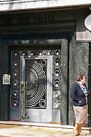 A front door to a beautiful building in central city with wrought iron gate designed in flower pattern, black marble around and a woman walking by. Montevideo, Uruguay, South America