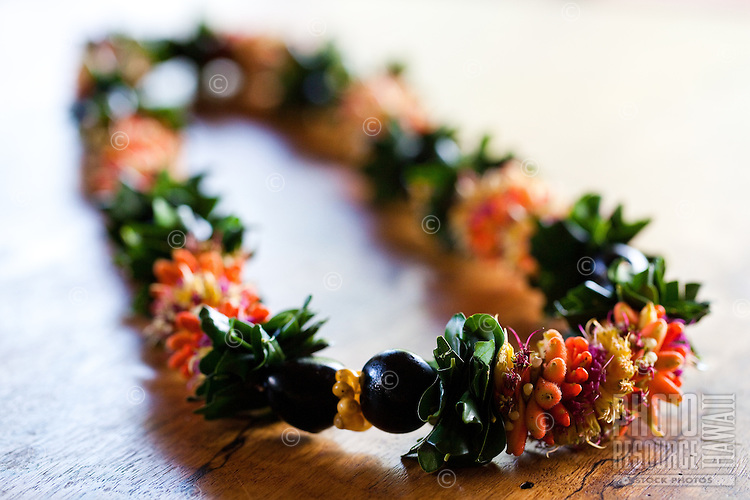 An orange, yellow and red cigar lei on a mango wood table