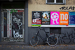 Posters, graffiti and a bicycle at the door of an apartment building in Sonnenalle, Germay. During 2015, Germany received around one million refugees fleeing conflict in the Middle East and parts of Africa. There were over 90 refugee help centres in the city by the end of that year.