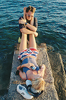 Spain. Ibiza in the Balearic islands. San Antonio. Mediterranean sea. A british couple (englishman and englishwoman). Both are young people. The man is in the water and holds up both legs of his girlfriend who lays and rests on rocks. She wears a pair of shorts with the english flag. © 1999 Didier Ruef