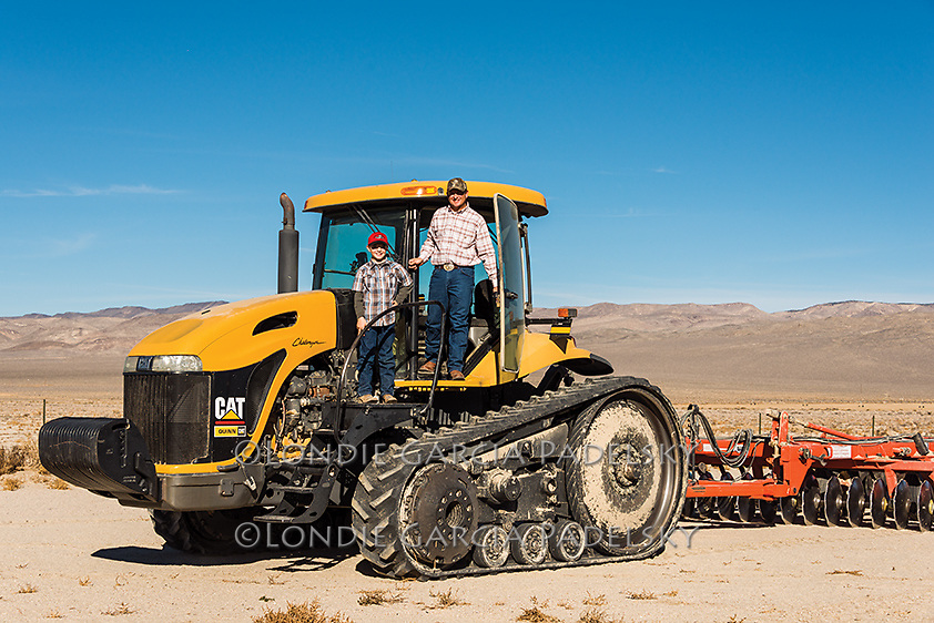 John Maurer and 10 year old son Cody plow the field in a Challenger MT765 Tractor<br /> pulling a disc and roller on the Triple D Ranch in Dyer, Nevada