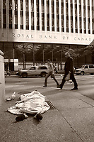 Pedestrians walk beside a homeless woman sleeping on the sidewalk facing  the Royal Bank of Canada building on King Street West in downtown Toronto, April 20, 2007.....    photo by Pierre Roussel - Images Distribution
