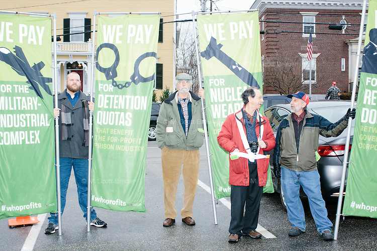 Members of the American Friends Service Committee's Governing Under the Influence Group hold banners outside before real estate mogul and Republican presidential candidate Donald Trump speaks at a rally at Exeter Town Hall in Exeter, New Hampshire, on Thurs., Feb. 4, 2016. The non-partisan group works to end militarization and corporate spending in American politics.