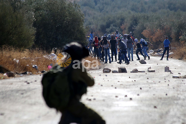 An Israeli soldier fires tear gas towards Palestinian protesters during clashes in the West Bank village of Tuqua, south-east of Bethlehem, on October 8, 2015. New violence rocked Israel and the Israeli occupied West Bank, including an incident in which men thought to be undercover Israeli police opened fire on Palestinian stone throwers they had infiltrated, wounding three of them. Photo by Muhesen Amren