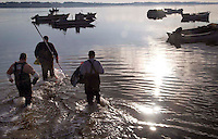 Jaime Resor, Dale Chadwick and Paul Fulcher, all from Harkers Island, waited for low tide at North River to wade out to their boats early Tuesday morning and go oystering, February 13, 2007. Beckley Fea_LowOysters