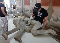 Restauratori al lavoro in un laboratorio negli scavi archeologici di Pompei per  un progetto di analisi restauro e conservazione che coinvolge 86 calchi di vittime dell'eruzione del vesuvio nel  del 79ac<br /> <br /> A restorer works on pietrified victim of eruption of Vesuvius in 79 BC in Pompeii in the laboratory  of excavation site . the project includes the study, preservation and restaration of 86 cast e tra due uomini l'abbraccio  di Pompei<br /> esame DNA sui calchi ha stabilito che u calchi appartenevano a due uomini non parenti tra di loro