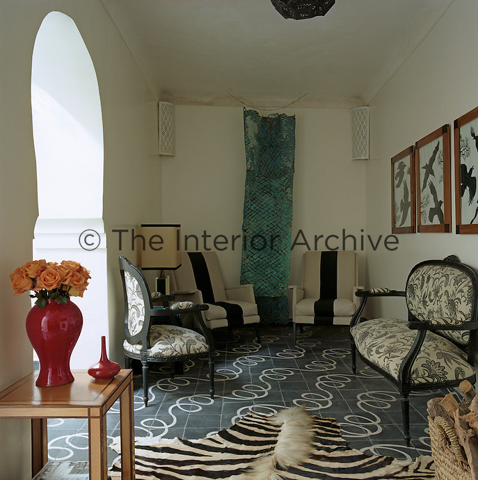 This end of the living room is dominated by a hanging copper artwork with black and white furniture on a tiled floor