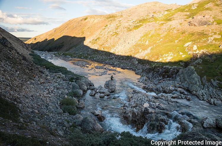 Mann fisker i kulp i Bjørnskardet, langt oppe i Komagelva. ---- Man fishing the upper parts of Komagelva.