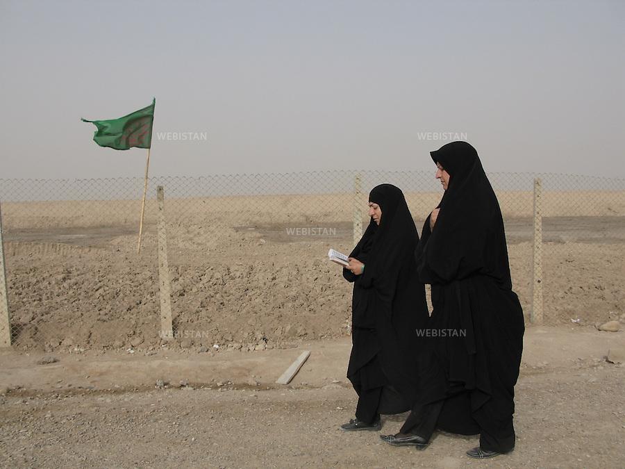 Iran. Khuzistan Province. Shalamcheh. March 22, 2009. Two women pray and walk on the martyr's footprints next to the remains of Iran-Iraq War (1980-1988) frontline zone, close to the Iraqi border. Every year, during the celebration of Nowrooz, the Iranian new year, thousands of Iranians from all over the country, called &quot;Rahian-e Noor&quot; (Caravan of light in Persian), helped by state organizations, gather on former battle fields to commemorate their loved ones who died as soldiers or Basijis. All expenses of this pilgrimage being paid by the State, makes it a favored touristic destination for  families of humble background. The Iran-Iraq War was one of the deadliest armed conflicts of the last quarter of the twentieth century, leaving one million victims.<br /> <br /> Iran. Province du Khouzistan. Shalamcheh. 22 Mars 2009.  Deux femmes prient et marchent sur les traces des martyres pr&egrave;s des restes de la ligne de front de la guerre Iran-Irak (1980-1988), pr&egrave;s de la fronti&egrave;re irakienne. Chaque ann&eacute;e, lors des c&eacute;l&eacute;brations de la f&ecirc;te de Norouz, le nouvel an iranien, des milliers d'iraniens de tout le pays, appel&eacute;s &quot;Rahian-e Noor&quot; (la caravane de lumi&egrave;re en persan), aid&eacute;s par des organisations gouvernementales, se rassemblent sur les anciens champs de batailles pour comm&eacute;morer leurs proches tomb&eacute;s comme soldat ou bassidji. La prise en charge totale des frais de d&eacute;placement et logement par l'&eacute;tat, font de ce p&egrave;lerinage un &eacute;vement touristique pris&eacute; des familles les plus mod&egrave;stes. La guerre Iran-Iraq fut l'un des conflits arm&eacute;s les plus meutriers du dernier quart du vingti&egrave;me si&egrave;cle, faisant environs un million de victimes.