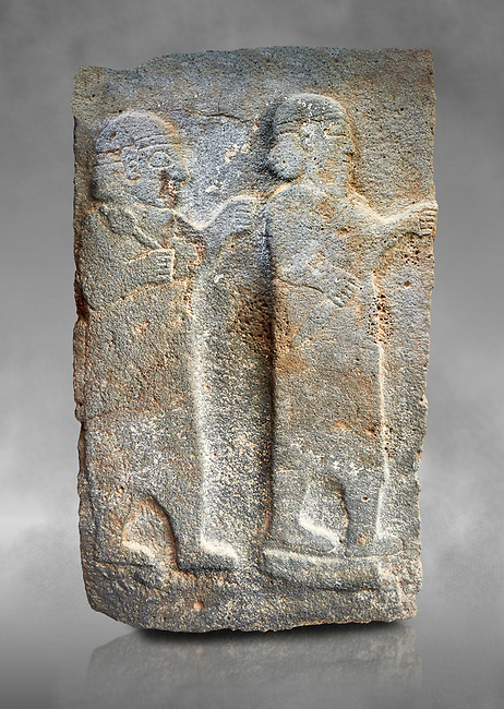 Pictures & images of the North Gate Hittite sculpture stele depicting Hittite Gods. 8th century BC. Karatepe Aslantas Open-Air Museum (Karatepe-Aslantaş Açık Hava Müzesi), Osmaniye Province, Turkey. Against grey art background