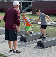 Graham Thomas/Herald-Leader<br /> Siloam Springs assistant football coach Tony Coffey leads Panther Academy participants through an agility drill on June 11 at Panther Stadium.