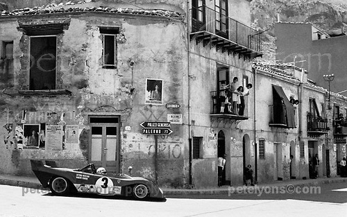 &quot;COLLESANO&quot; <br /> aka TARGA FLORIO FERRARI<br /> <br /> SICILY, MAY 21, 1972 ... There we were, idling away a warm springtime day in the ancient Mediterranean town of Collesano, when we heard the 20th Century coming down on us. Something was plunging from the craggy mountains above, something wild, its untamed cry reverberating between the timeworn buildings. The wise among us took cover in doorways. I raised my Nikon. Around the corner, a flash of scarlet. The Ferrari. I framed and fired. And the moment was gone.<br /> <br /> For me this picture brings it all back, and it also seems to speak to many who were never there but wish they had been. Visitors in our vendor booth at Monterey often pick it up to show their friends, and they talk about it with animation and shining faces.<br /> <br /> A blood-red racing car screaming across the open landscapes of Olde Europe. The mad delirium that sparked our passion.<br /> <br /> This was the crazy-wonderful old Targa Florio, one of the world's most venerable road races, and among the most endangered. It had been going for 66 years when I was there in 1972, but that was its next to last year as an important International event.  Too dangerous, was the bleat coming from all sides. Sure, it was, but so what? I went there to stand up for it.<br /> <br /> For me, that day remains one of the most magical  I ever spent at motor racing. <br /> <br /> Though we colloquially call this picture just &quot;Collesano,&quot; its proper file ID is SC72Targa_Ferrari3CollesanoB