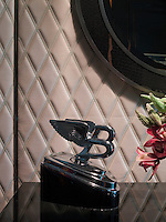 A sculpture of the renowned Mulsanne bonnet mascot, the Flying B, sits on a console table in the foyer against the neutral colour of the leather wall covering