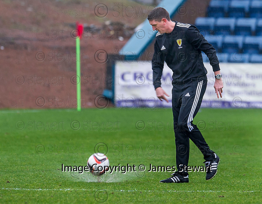 Referee Craig Thomson checks out the Dens Park pitch before calling the game off just before 2.00 pm.