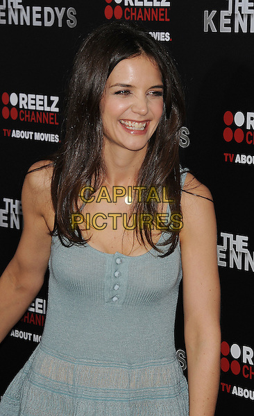 "KATIE HOLMES.arriving at the world premiere of ""The Kennedys"" held at the Samuel Goldwyn Theatre at the Academy of Motion Picture Arts and Sciences in Beverly Hills, California, USA, March 28th, 2011. .half length knitted dress smiling make-up beauty green blue buttons vest sleeveless S initial necklace gold letter.CAP/ROT/TM.© TM/Roth/Capital Pictures"