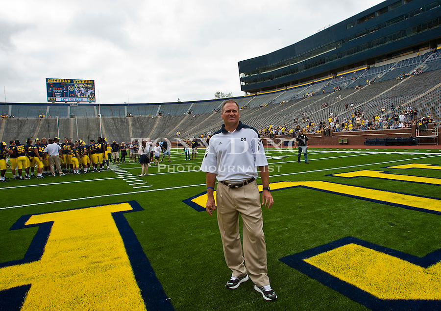 Michigan head coach Rich Rodriguez surveys Michigan Stadium as his players gather for a team photo session, during the annual NCAA college football media day, Sunday, Aug. 22, 2010, in Ann Arbor, Mich. (AP Photo/Tony Ding)
