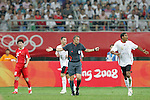 10 August 2008: Referee Hector Baldassi (ARG) (center) indicates that he did not see a foul.  The men's Olympic soccer team of Belgium defeated the men's Olympic soccer team of China 2-0 at Shenyang Olympic Sports Center Wulihe Stadium in Shenyang, China in a Group C round-robin match in the Men's Olympic Football competition.